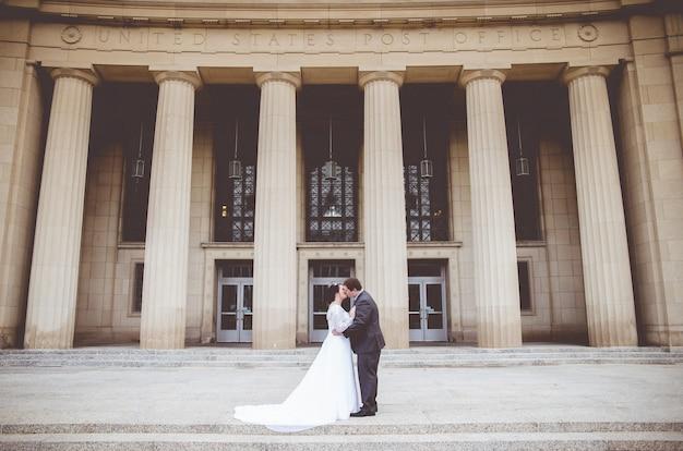 Mężczyzna całuje kobietę w dniu ślubu