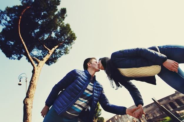 Mężczyzna całuje kobietę w nosie przed koloseum