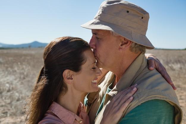 Mężczyzna całuje kobiety czoło na krajobrazie
