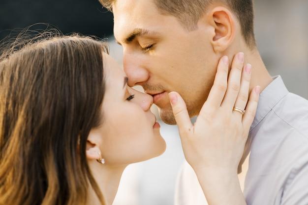 Mężczyzna całuje nos swojej kobiety, pocałunek z bliska