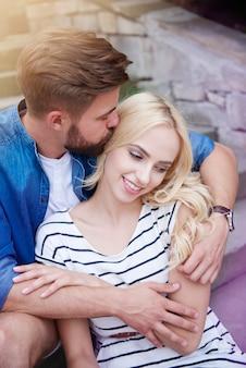 Mężczyzna całuje swoją kobietę na schodach