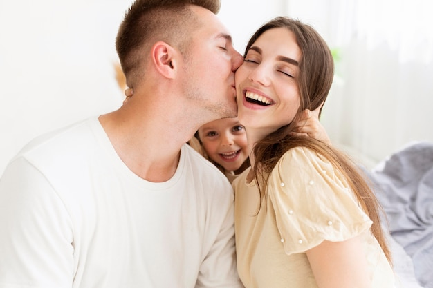 Mężczyzna całuje żonę w policzek obok córki