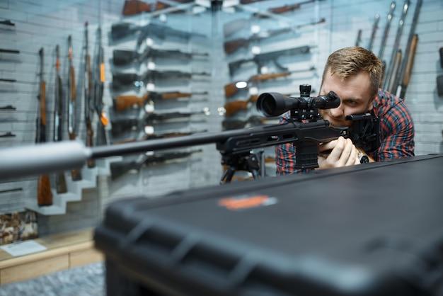 Mężczyzna celuje z karabinu snajperskiego w sklepie z bronią