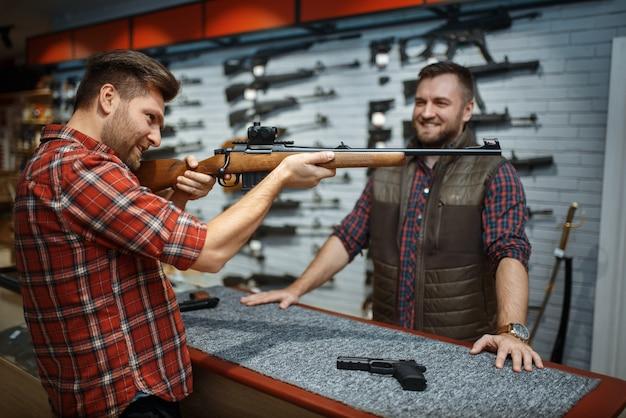 Mężczyzna celuje z nowym karabinem, sprzedawca przy ladzie w sklepie z bronią. mężczyzna kupuje broń w sklepie, polowanie i strzelectwo sportowe