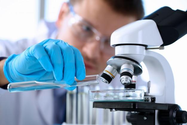 Mężczyzna chemik trzyma w ręku szklaną probówkę