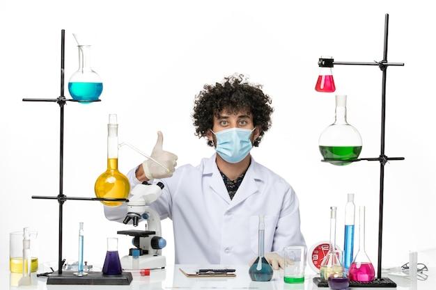 Mężczyzna chemik z widokiem z przodu w białym kombinezonie medycznym iz maską po prostu siedzący z różnymi roztworami na białej przestrzeni