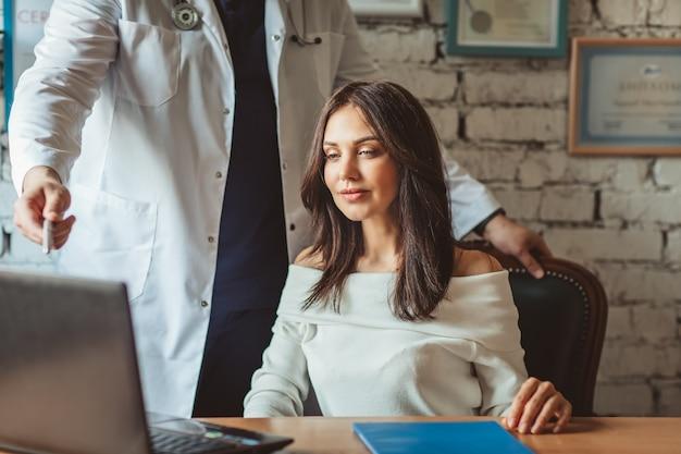 Mężczyzna chirurg lekarz w mundurze medycznym ze stetoskopem po konsultacji z atrakcyjnym pacjentem w gabinecie.