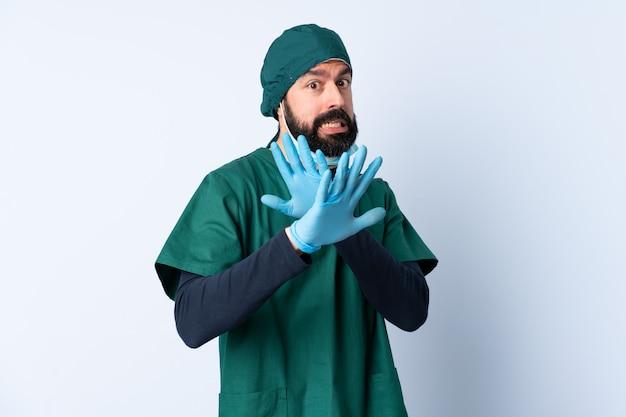 Mężczyzna chirurg w zielonym mundurze na ścianach nerwowe rozciąganie rąk