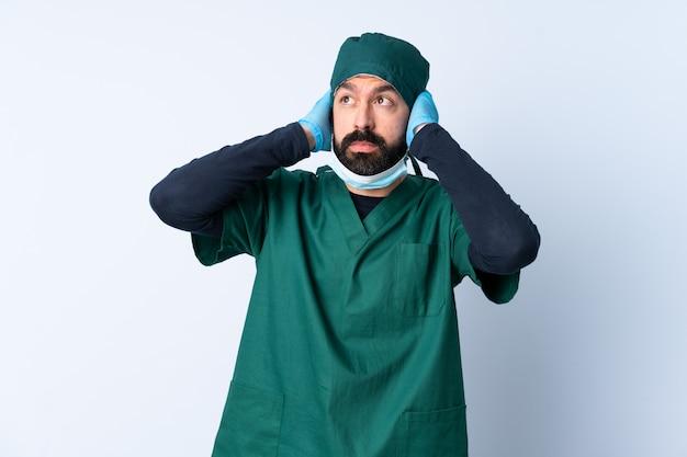 Mężczyzna chirurg w zielonym mundurze na ścianie sfrustrowany i obejmujące uszy