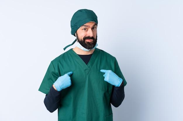Mężczyzna chirurg w zielonym mundurze na ścianie, wskazując na siebie