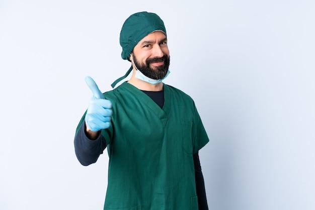 Mężczyzna chirurg w zielonym mundurze na ścianie z kciukami do góry, ponieważ stało się coś dobrego
