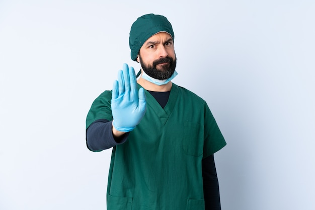 Mężczyzna chirurg w zielonym mundurze nad ścianą co zatrzymać gest