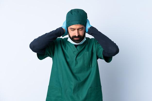Mężczyzna chirurga w zielonym mundurze na pojedyncze ściany sfrustrowany i obejmujące uszy