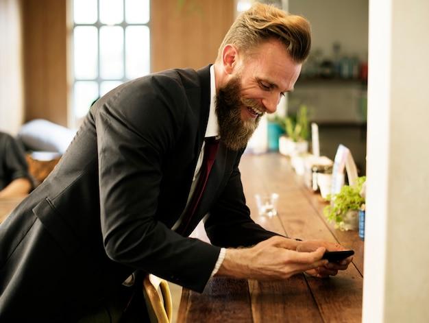 Mężczyzna chłodzi out przy sklep z kawą z telefonem komórkowym