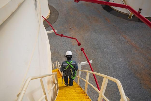 Mężczyzna chodzący po schodach inspekcja wizualna zapis uprzęży bezpieczeństwa zbiornika pracy na wysokości.