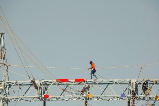 Mężczyzna chodzenie po stalowej belce montaż słupów wysokiego napięcia przesyłu energii elektrycznej praca on-line na wysokości ryzyko należy nosić bezpieczną pełną uprząż