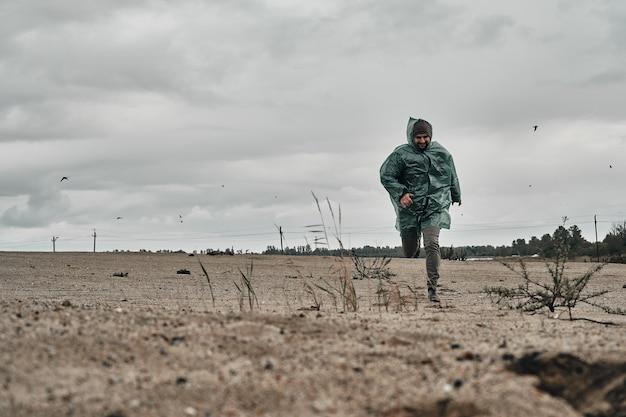 Mężczyzna chodzi po piasku w deszczu w zielonym płaszczu przeciwdeszczowym.