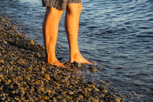 Mężczyzna chodzi samotnie na żwirowej plaży w zmierzchu
