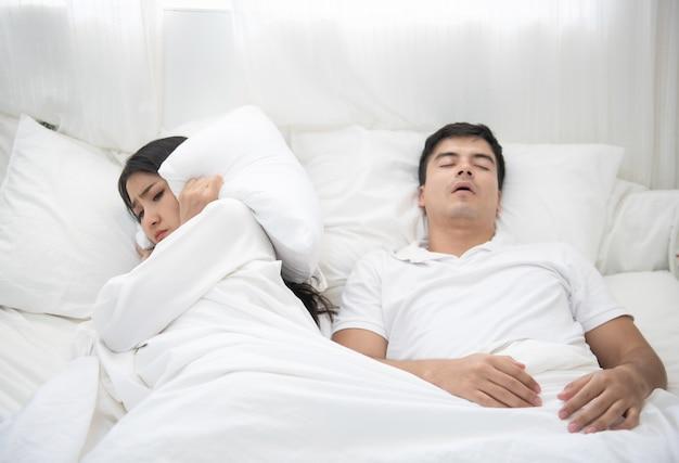 Mężczyzna chrapie, kobieta nie może spać w łóżku w domu.