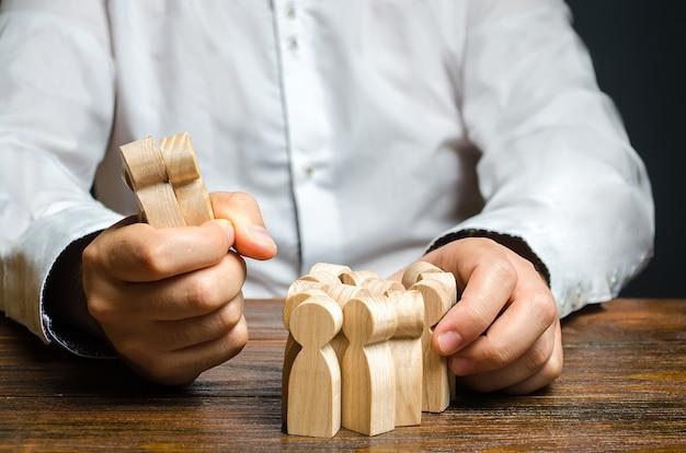 Mężczyzna chwyta figurkę ludzi z tłumu zatrudnianie pracowników segmentacja rynku