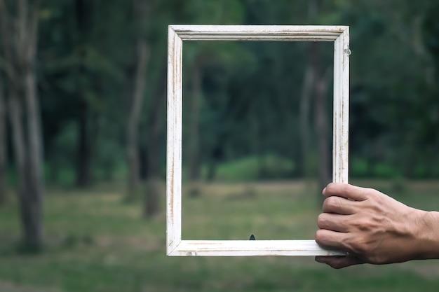 Mężczyzna chwyta podłego szyka stylu rocznika drewnianej drewnianej ramy plamy zieleni natura