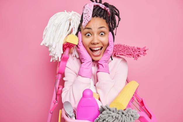 Mężczyzna chwyta zaopatrzenie twarzy z usługą sprzątania otoczoną sprzętem niezbędnym do sprzątania pokoju na różowym tle