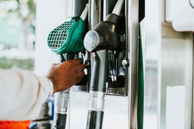 Mężczyzna chwytający dyszę paliwową, by zatankować swój pojazd