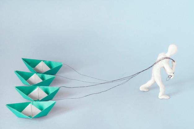 Mężczyzna ciągnie na linach cztery papierowe zielone łodzie. koncepcja biznesu, sukces, ciężka praca.