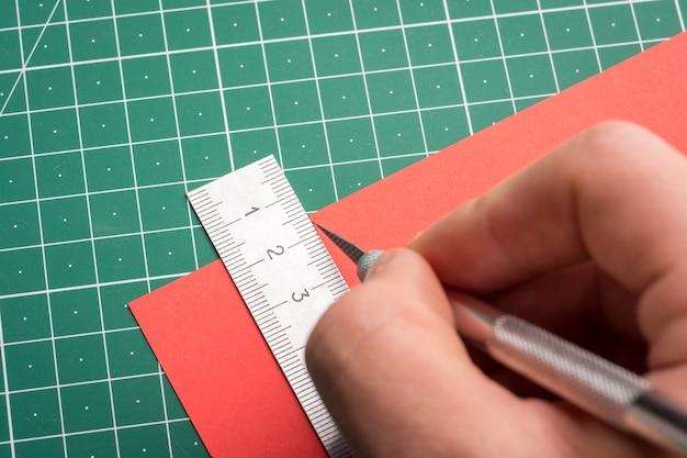 Mężczyzna cięcia czerwonego papieru za pomocą skalpela papieru