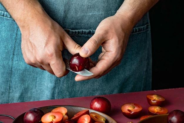 Mężczyzna cięcia czerwonych śliwek w kuchni