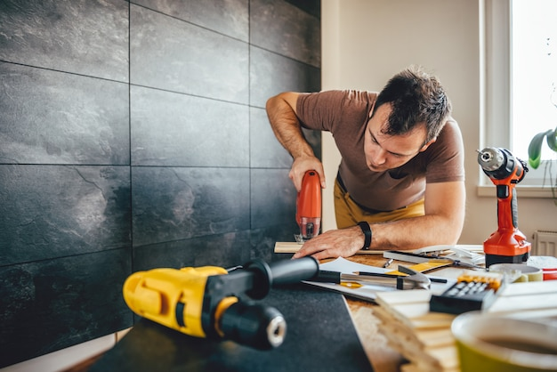 Mężczyzna cięcia drewna za pomocą elektrycznej wyrzynarki