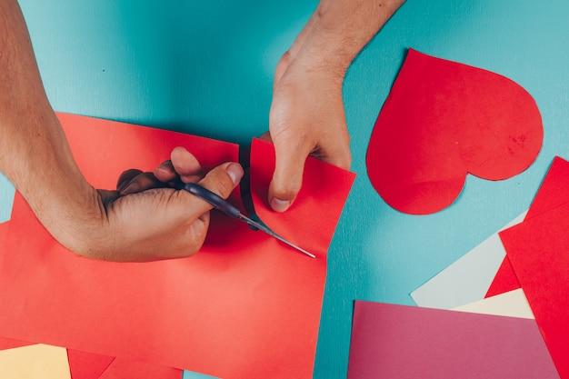 Mężczyzna cięcia kształtów z kolorowych papierów na niebiesko-niebieski