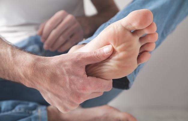 Mężczyzna cierpi na ból stopy.