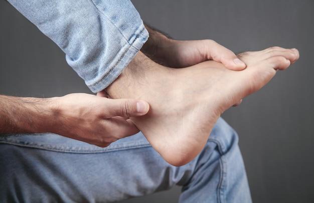 Mężczyzna cierpiący na ból stopy.