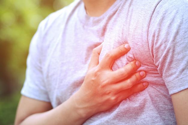 Mężczyzna cierpiący na ból w klatce piersiowej - zawał serca powoduje szok na sofie w salonie. lub jeśli kwas kolkowy powraca do klatki piersiowej. koncepcja opieki zdrowotnej.