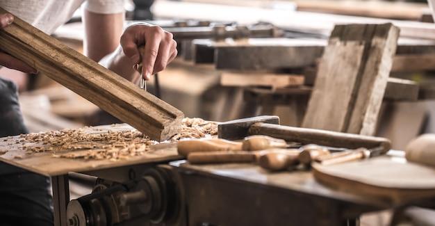 Mężczyzna cieśla pracujący z wyrobem z drewna, narzędzia ręczne