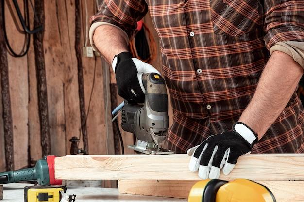 Mężczyzna cieśla ścina drewnianą belkę za pomocą elektrycznej wyrzynarki, męskie dłonie z elektryczną układanką.