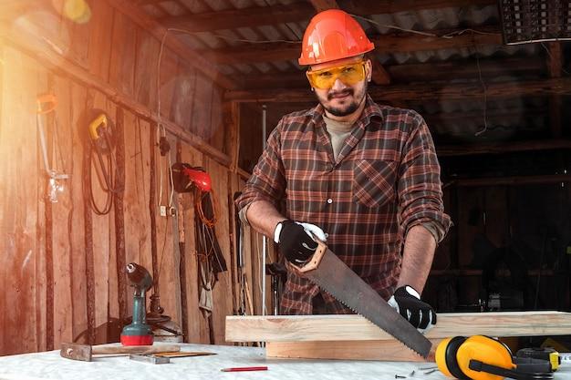 Mężczyzna cieśla ścina drewnianą belkę za pomocą piły ręcznej, męskie dłonie z piłą zbliżenie.