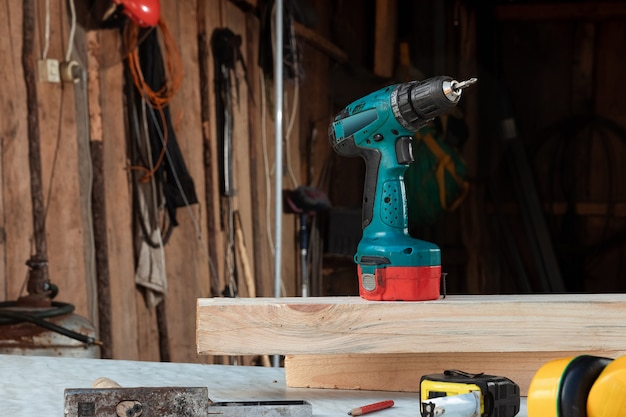 Mężczyzna cieśla wkręca śrubę w drzewo elektrycznym śrubokrętem, męskie dłonie z bliska śrubokrętem.