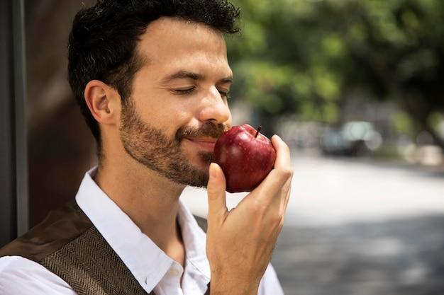Mężczyzna cieszący się jabłkiem na zewnątrz