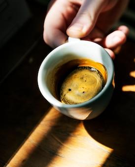 Mężczyzna cieszy się filiżankę gorąca kawa w kawiarni