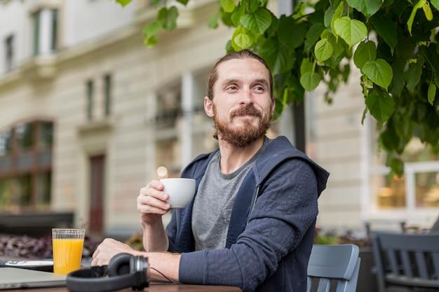 Mężczyzna cieszy się kawę przy miasto tarasem