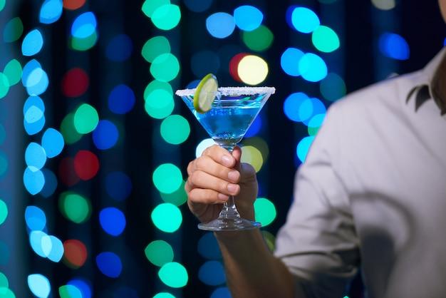 Mężczyzna cieszy się koktajl przy przyjęciem