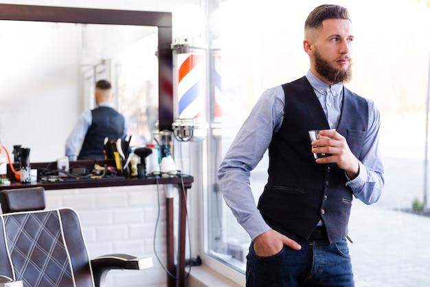 Mężczyzna cieszy się napój przy salonem
