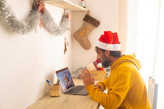 Mężczyzna cieszy się świąteczną konferencją telefoniczną z kobietą na laptopie