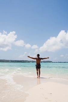 Mężczyzna cieszy się światłem słonecznym na plaży