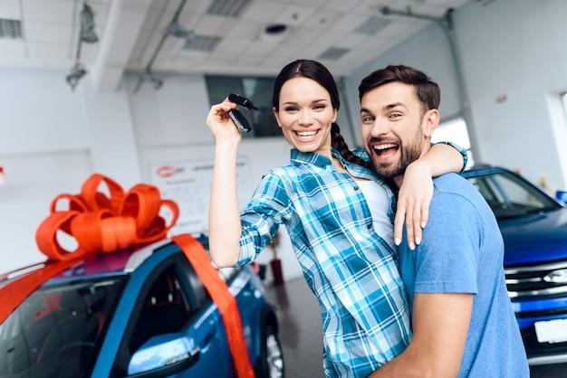 Mężczyzna cieszy swoją żonę nowym samochodem.