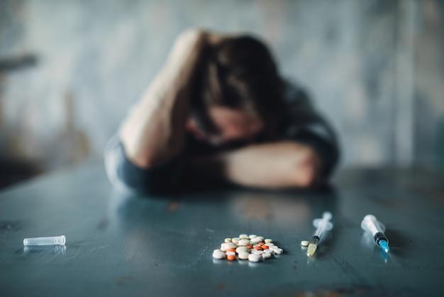 Mężczyzna ćpun przy stole z lekami i strzykawką