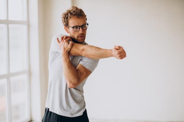 Mężczyzna ćwiczący jogę na macie w domu