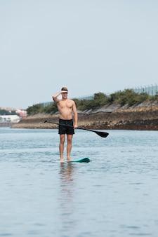 Mężczyzna ćwiczący surfing wiosłowy
